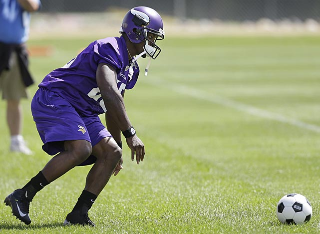 Minnesota Vikings running back Adrian Peterson looks to pick up a soccer ball during a training camp drill in Mankato, Minn.
