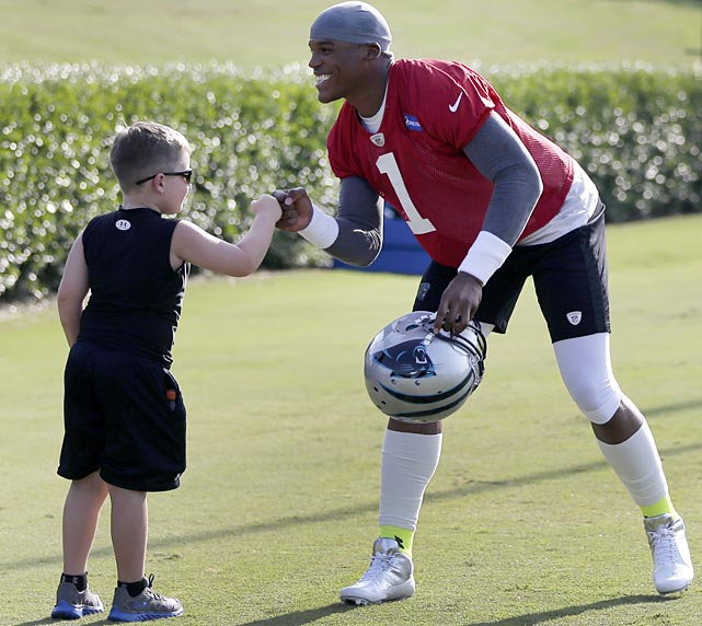Carolina Panthers quarterback Cam Newton gives a fist-bump to Max Kalinowski, 6, of Spartanburg, S.C., during camp in Spartanburg.