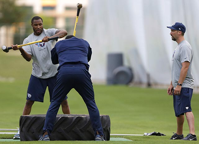 Tennessee Titans strong safety Robert Johnson, left, and tight end Delanie Walker, center, work out with sledgehammers under the watch of assistant athletic trainer Don Moseley. Both players are on the injured reserve roster.