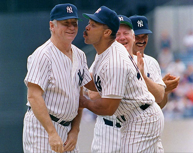 Mickey Mantle gets a kiss from Reggie Jackson during the Yankee's 45th Annual Old Timers Classic ceremony at Yankee Stadium.