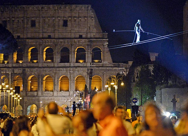 Tightrope walker Andrea Loreni performs in front of the Coliseum in Rome.