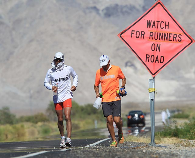 Ray Sanchez (left_ of Sacramento runs along highway 136 during the AdventurCORPS Badwater 135 ultra-marathon outside of Death Valley National Park, Calif. Billed as the toughest footrace in the world, competitors run 135 miles nonstop over three mountain ranges.