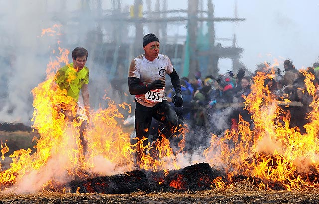 A competitor runs through fire during the Tough Guy Challenge in Telford, England. Every year, thousands of people run the eight-mile assault course, which involves freezing temperatures, fire, and ice
