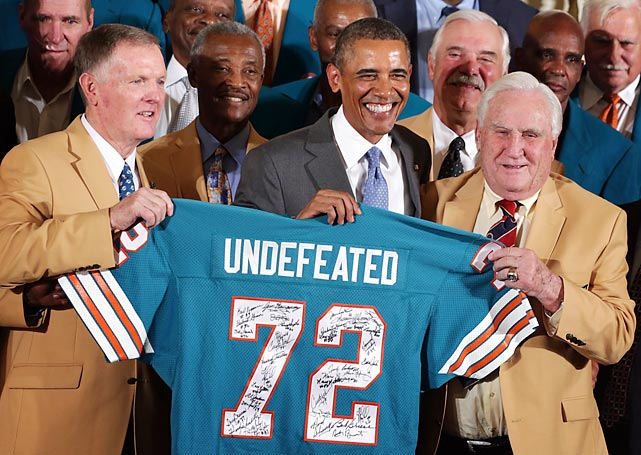 Nice to see the Fish are finally getting their due. President Barack Obama thought it was time that someone acknowledged their undefeated season, so he invited quarterback Bob Griese (left), running back Larry Csonka (behind the left shoulder of the POTUS) and head coach Don Shula (right), among others to a solemn ceremony at the White House.