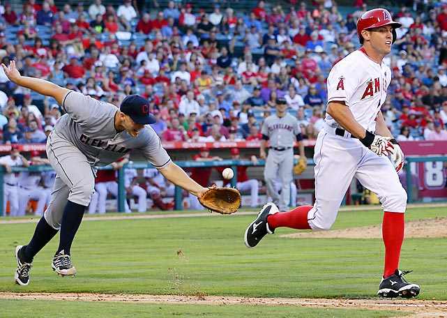 Cleveland Indians pitcher Justin Masterson tosses the ball to first baseman Nick Swisher for the out on Los Angeles Angels' Peter Bourjos.