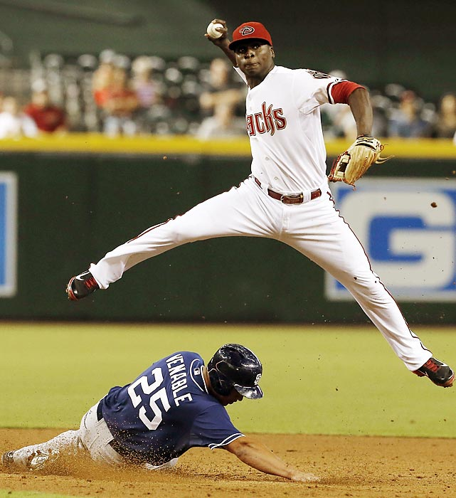 Diamondbacks shortstop Didi Gregorius leaps over the Padres' Will Venable for a throw to first on Aug. 26. Though his bat has slumped after a hot start, Gregorius has stayed in the Arizona lineup by playing sparkling defense.