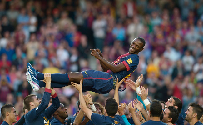 Eric Abidal is lifted into the air by his teammates in June after his final match with Barcelona.