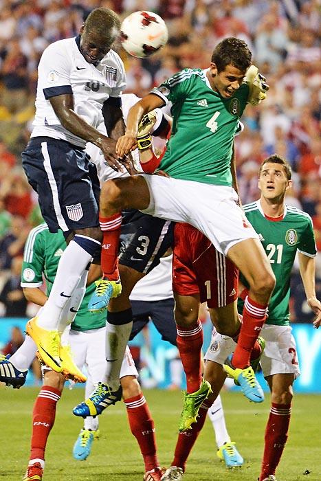 U.S. striker Eddie Johnson (18) heads the ball past defender Diego Reyes (4) and goalie Jesús Corona (1, background in red shorts) of Mexico for the first goal of the American's 2-0 victory on Sept. 10. The win, coupled with a 2-2 draw later the same evening between Honduras and Panama, clinched a berth for the U.S. in the 2014 World Cup.