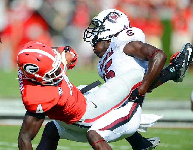 South Carolina cornerback Jimmy Legree (15) gets his helmet knocked askew while taking down Georgia tailback Keith Marshall (4) during the Bulldogs 41-30 defeat of the Gamecocks on Sept. 7.