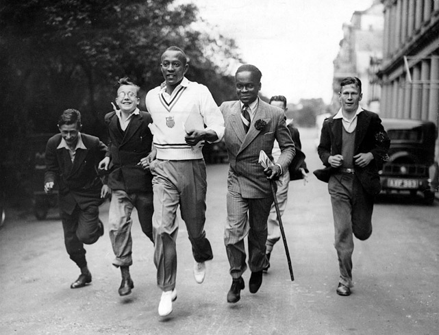 During a visit to London in Aug. 1936, Owens is accompanied by some admirers on his morning run.