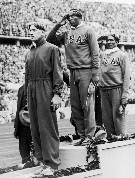 Owens salutes during the presentation of his gold medal for the 100m sprint event on Aug. 4, 1936. U.S. teammate Ralph Metcalfe won the silver and Martinus Osendarp of Holland won the bronze.