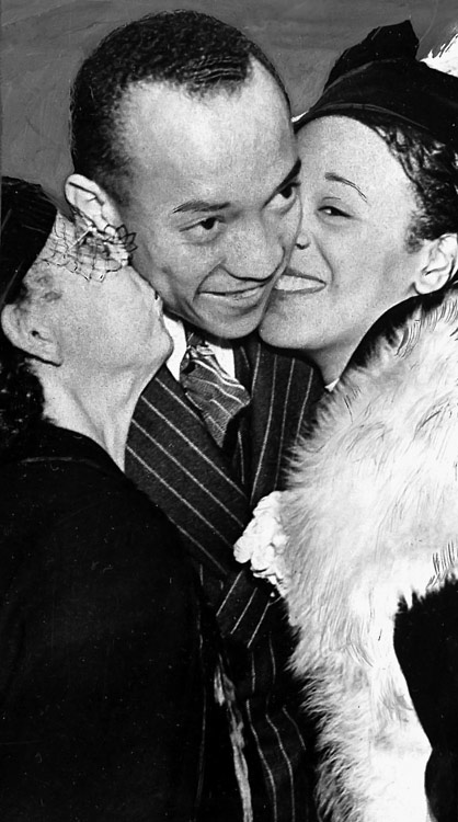 Owens is kissed upon arrival in New York aboard the liner Queen Mary by his mother and his wife on Aug. 31.