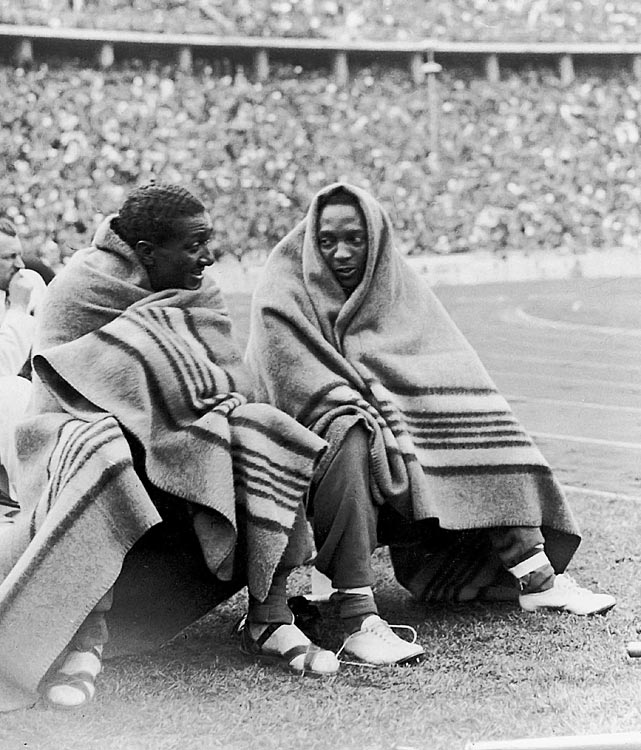 Jesse Owens and Ralph Metcalfe (left) keep warm under blankets during the 100m finals at the Berlin games on Aug. 4, 1936. The pair won gold and silver medals respectively.