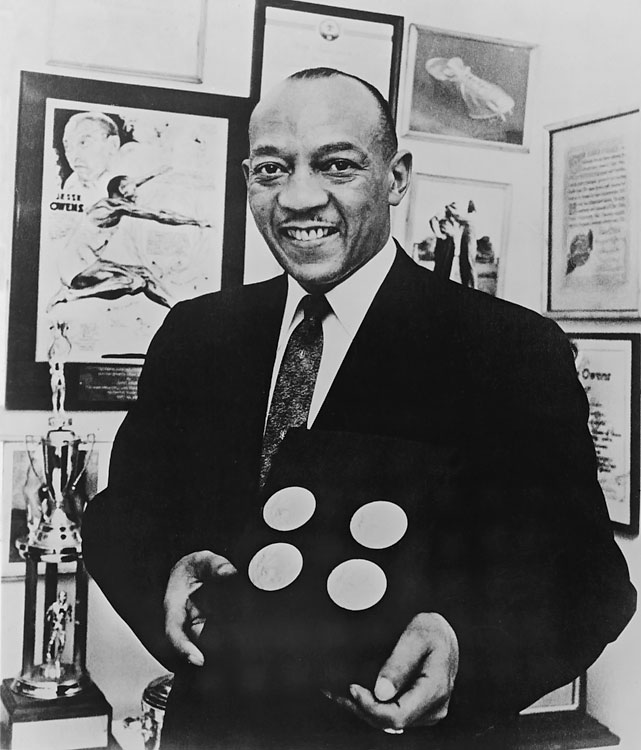 Owens smiles as he poses in 1951 with the four gold medals he won at the 1936 Berlin Olympics.