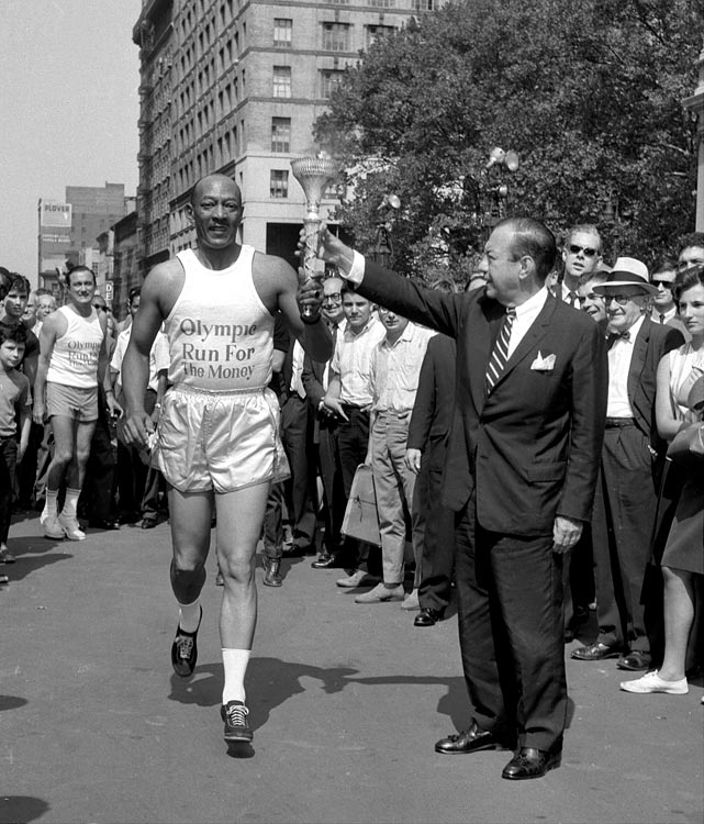 Owens takes the torch from New York City Mayor Robert Wagner at City Hall. Owens was the first of 3,500 runners to span the nation on a cross-country run to raise funds for the 1964 Olympic team.