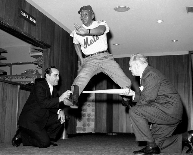Owens flashes his old technique from the 1936 Olympics for Mets GM George Weiss (right) and coach Yogi Berra at Shea Stadium in February 1965. Owens was hired by the Mets as a running instructor during spring training sessions at St. Petersburg, Fla.