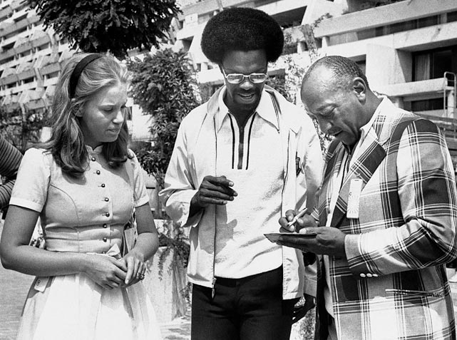 Owens signs an autograph for a Munich Olympic hostess on Aug. 24, 1972, while talking with 1960 Olympic gold medal winner for the long jump, Ralph H. Boston, a member of the U.S. Olympic Committee.