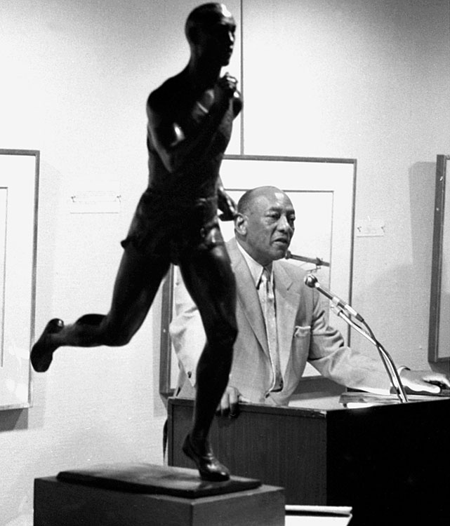 Owens praises his country as he speaks near a statue of himself as an Olympic runner at Madison Square Garden in New York City on Aug. 25, 1976. Owens died on March 31, 1980.