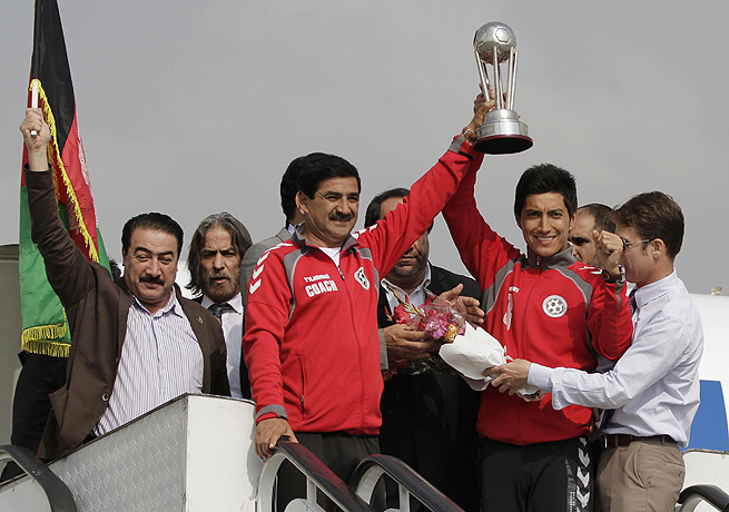 Afghanistan coach Yusuf Korgar (with trophy) led his team to its first international championship.