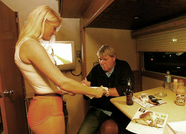 Just another day at the office for John Daly at the 2007 Masters as he signs an autograph for a Hooters girl. Daly did not compete in the tournament, but he had plenty (cigarettes, beer, Hustler) to keep him occupied.