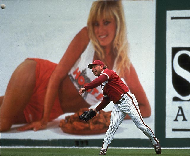 Phillies outfielder Lenny Dykstra fields a ball beneath the eerie gaze of a Hooters girl. This, however, wasn't any Hooters girl. The blonde in question was actually the wife of teammate Darren Daulton.