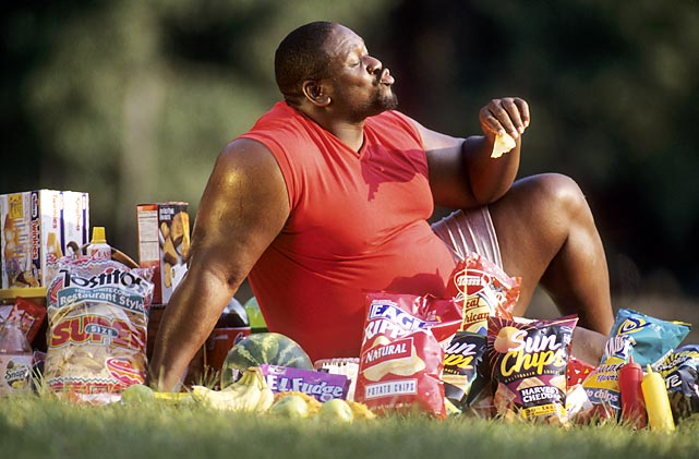 """Dallas Cowboys lineman Nate Newton is on the """"eat everything"""" diet as he samples from every snack imaginable during a 1995 SI photo shoot."""