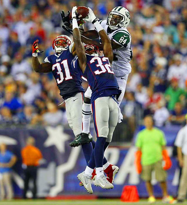 New England Patriots defensive backs Devin McCourty (32) and Aqib Talib (31) go airborne to fight New York Jets receiver Stephen Hill for the ball.