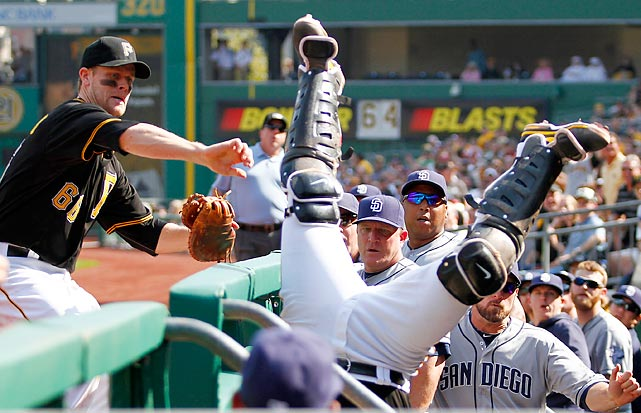 Pittsburgh Pirates catcher Tony Sanchez tumbles over the railing after catching a foul ball against the San Diego Padres. The Pirates won 10-1 and clinched a playoff berth for the first time in 21 years four days later.