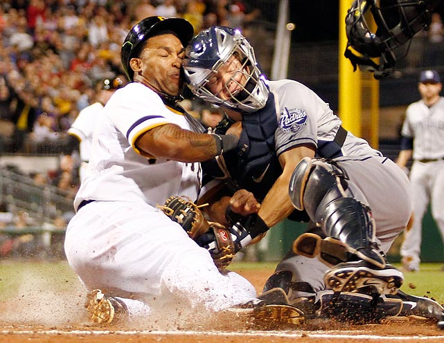 San Diego Padres catcher Nick Hundley holds onto the ball to tag out Pittsburgh Pirates outfielder Marlon Byrd in a play at the plate.