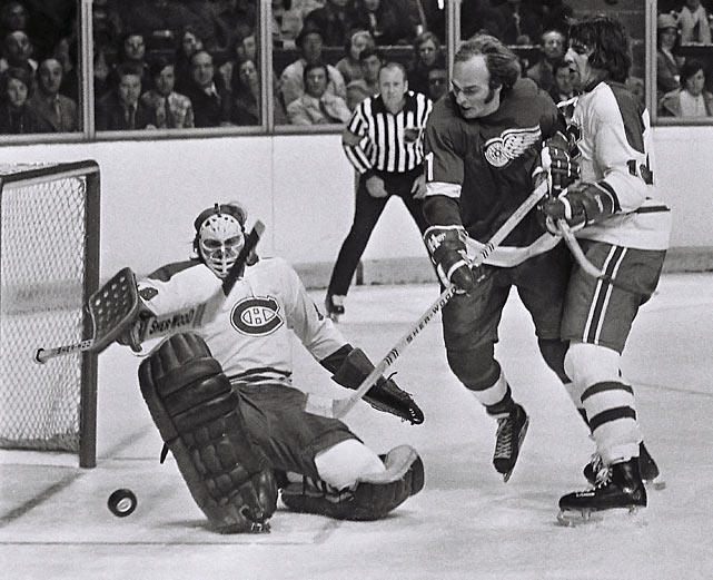 Canadiens goalie Ken Dryden blocks the puck while teammate Serge Savard helps defend the goal against the Red Wings' Leon Rochefort during a game at the Montreal Forum circa 1972.