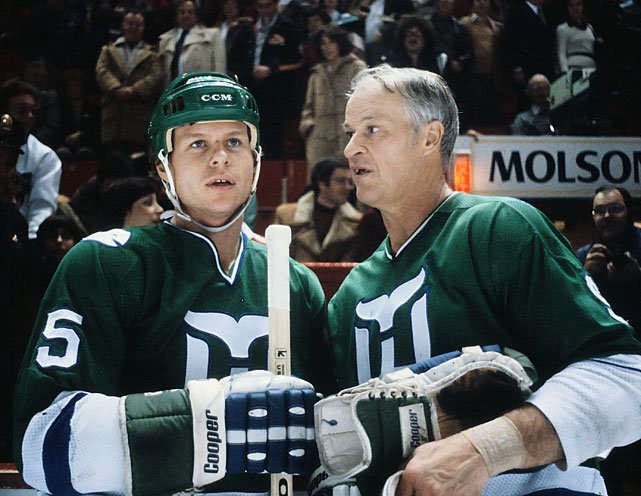 Hartford Whalers Gordie Howe and son Mark Howe chat in a game against the Canadiens in Montreal during the 1979-80 season.