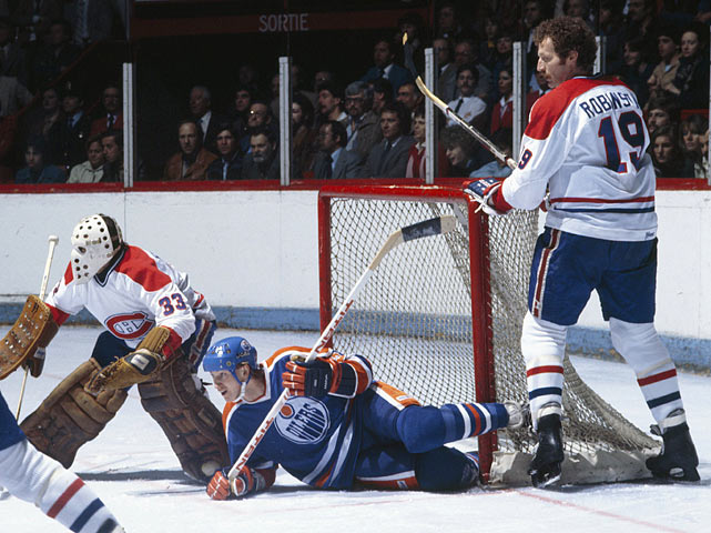 The Oilers' Wayne Gretzky falls in the crease between Canadiens goalie Richard Sevigny and defenseman Larry Robinson during a game at the Montreal Forum in the early 1980s.