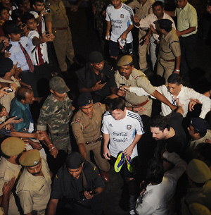 Security escorts Lionel Messi through a crowd of fans in Kolkata before a practice session.
