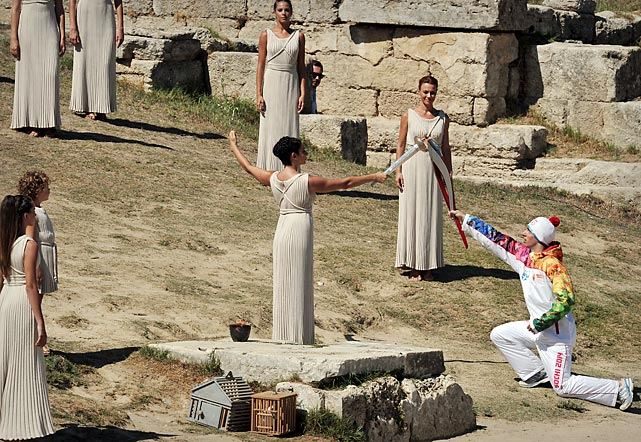 Greek actress Ino Menegaki passed the flame to the first Sochi Winter Games torch bearer, Greek skier Giannis Antoniou, during the solemn ceremony in ancient Olympia, where the Olympics and their myriad official products were born in 776 BC.