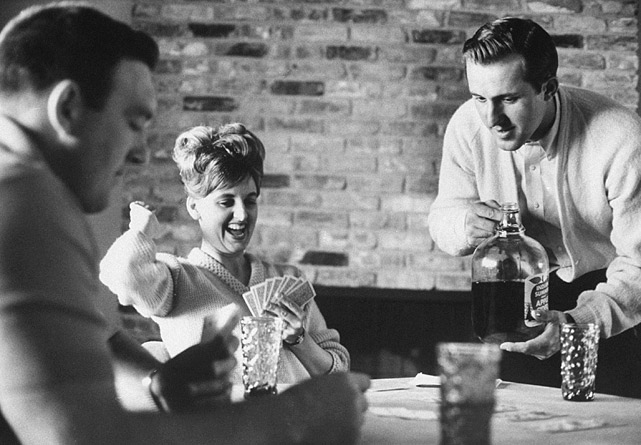 Minnesota Vikings quarterback Fran Tarkenton looks to pour himself some apple cider while he and his wife, Elaine, play bridge with friends at home, circa 1965.