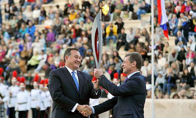 Russian Deputy Prime Minister Dimitry Kozak (right) received the Olympic flame in a handover ceremony in Athens.