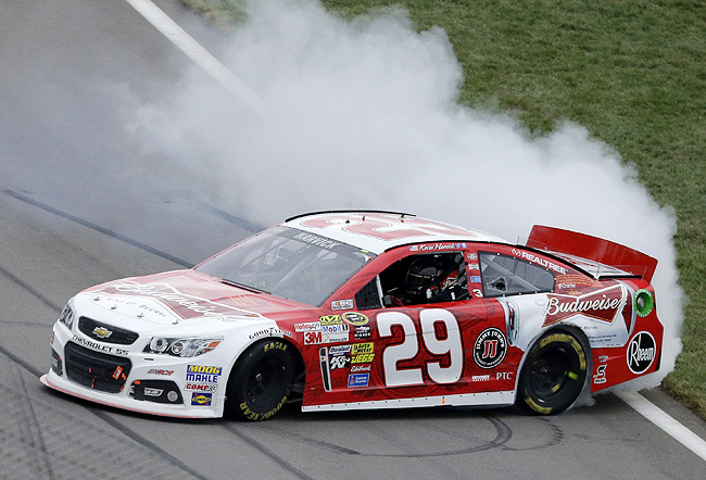 Harvick pulled away from Kurt Busch and Jeff Gordon on a late restart to win a wreck-filled race.