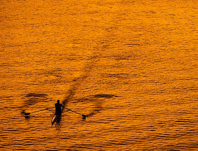 A lone boater skims across the surface of the Potomac River at sunset in Washington on Oct. 8.