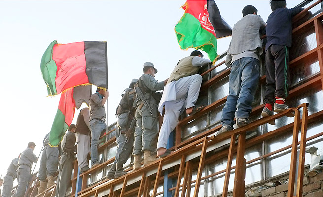 Afghan fans climb the fence around the stadium to get a glimpse of their national team in action.