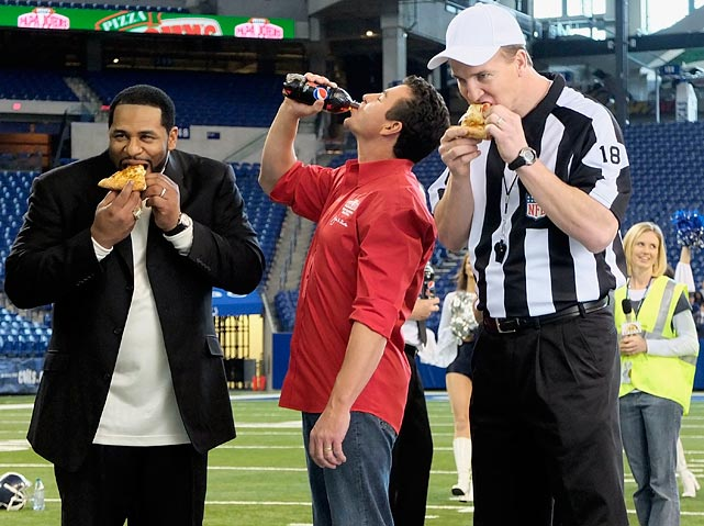 Manning and Bettis eat some Papa John's pizza alongside Founder, Chairman and CEO John Schnatter during a commercial shoot at Lucas Oil Stadium in Indianapolis.