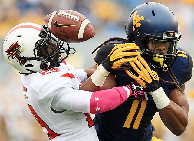 Texas Tech defensive back Olaoluwa Falemi breaks up a pass intended for West Virginia wide receiver Kevin White. The No. 16 Red Raiders needed a fourth-quarter rally to beat the Mountaineers, 37-27.