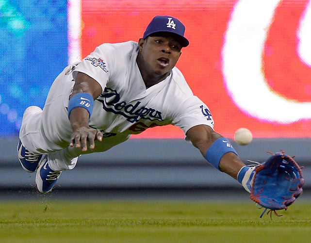 Los Angeles Dodgers outfielder Yasiel Puig can't quite reach a ball hit by St. Louis Cardinals third baseman David Freese in Game 3 of the NLCS. The Cardinals won the series 4-2, and will face the Boston Red Sox in the World Series.