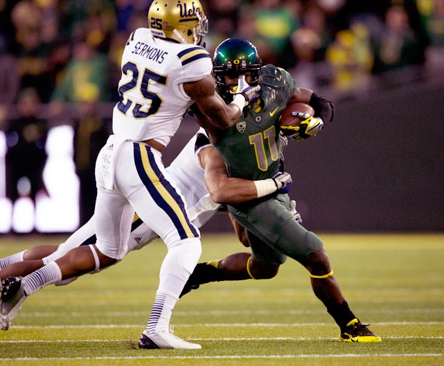 Oregon wide receiver Bralon Addison is dragged down by two UCLA defenders.