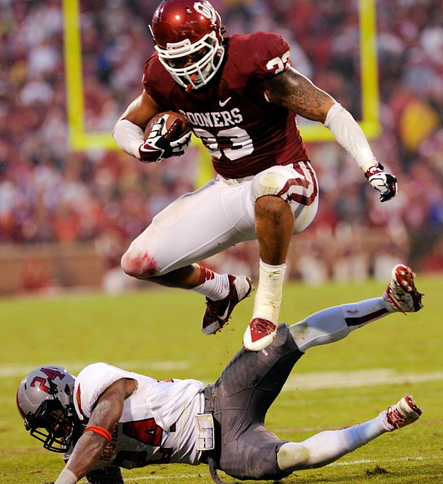 Oklahoma running back Trey Millard hurdles Texas Tech defensive back Bruce Jones. The Sooners handed the Red Raiders their first loss of the season, 38-30.