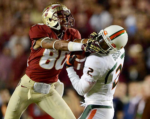 Florida State wide receiver Rashad Greene gets a handful of Miami defensive back Deon Bush's facemask after Bush intercepted Jameis Winston.