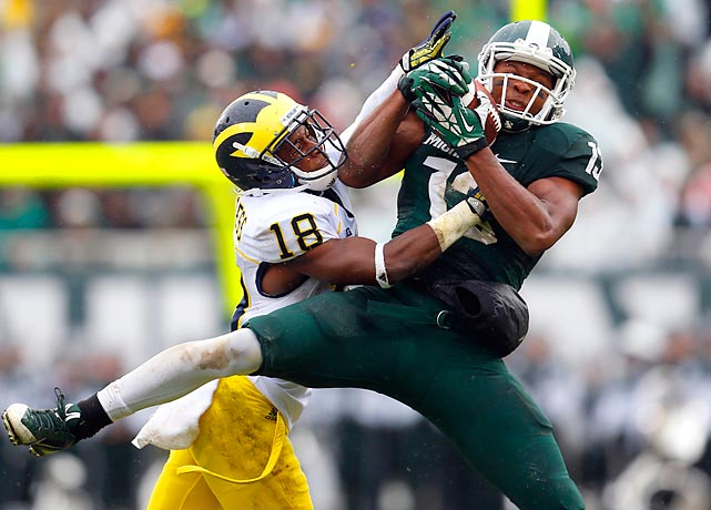 Michigan State wide receiver Bennie Fowler fights for a pass in front of Michigan defensive back Blake Countess. The Spartans handled the Wolverines easily in the rivalry game, winning 29-6.