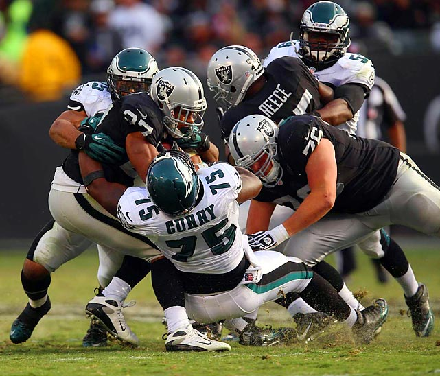 Eagles defenders gang tackle Raiders running back Rashad Jennings.