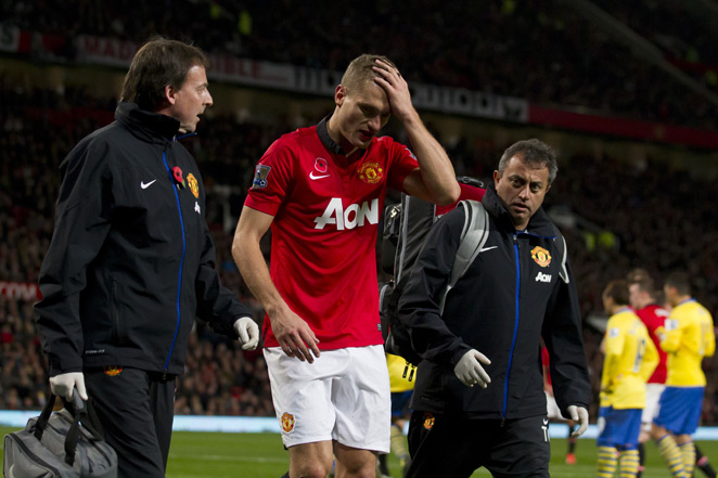 Manchester United captain Nemanja Vidic walks off the field after suffering a concussion against Arsenal Sunday.
