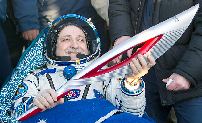 Fyodor Yurchikhin holds the Olympic torch after returning with it from the International Space Station.