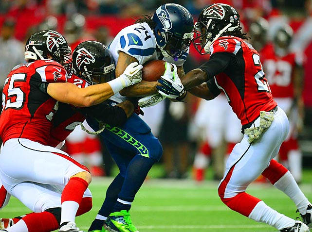 """Seahawks running back Marshawn Lynch lives up to his """"Beast Mode"""" nickname as he runs through three Atlanta Falcon defenders. Lynch finished with 145 yards and a score on 24 carries."""
